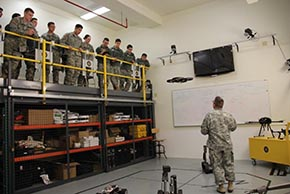 LTC Korpela demonstrates a drone-like robot while cadets also observe classmates driving other robots