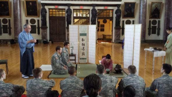 Cadets David Jerome and Patrick Monfort participate in the Japanese Tea Ceremony. The Kanji characters on the scroll mean harmony, respect, purity, and tranquility.