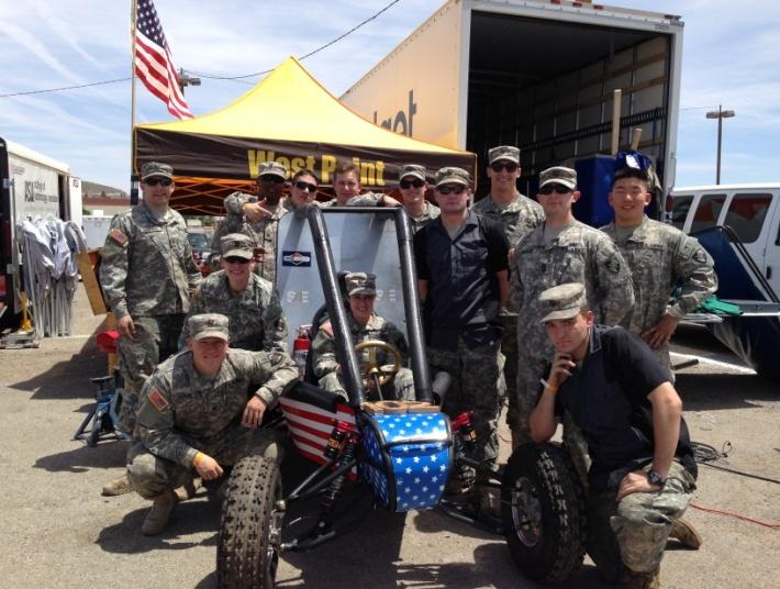 The thirteen cadets on the 2014 Mini Baja team with their off-road vehicle prototype.