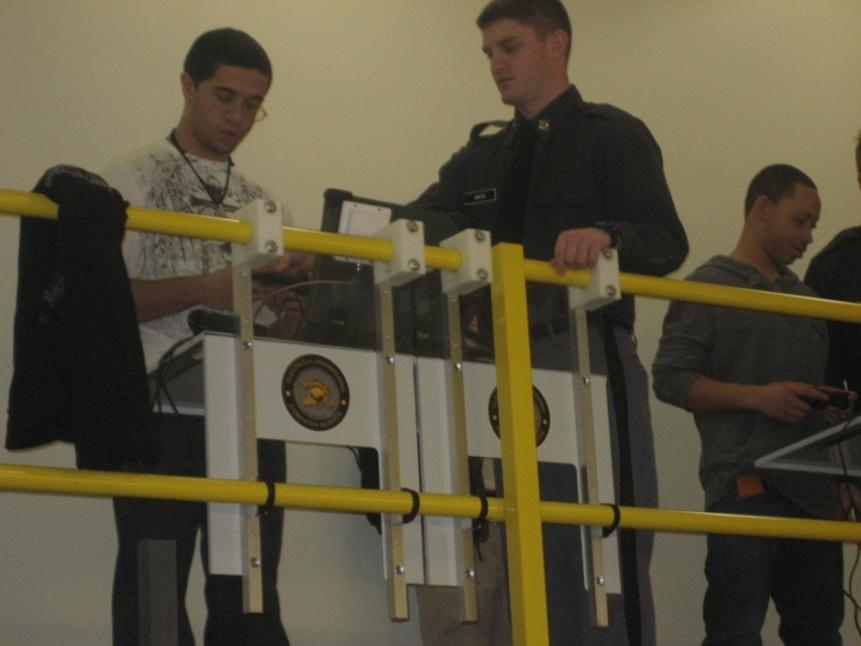 Cadet Patrick Smith assists a student with the controls of the Packbot.