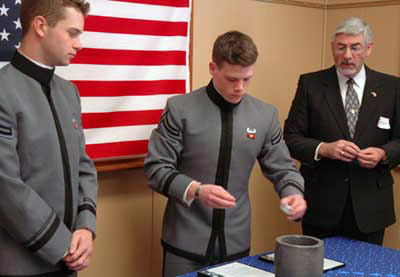 After all donated rings were added to the crucible, Cadet Tim Allen '07, Chair of the Ring and Crest Committee, pours some of the sample for the previous year's melt into the crucible as Class VP Tim O'Connor, Tony Ferraiuolo (Honorary '61) look on.
